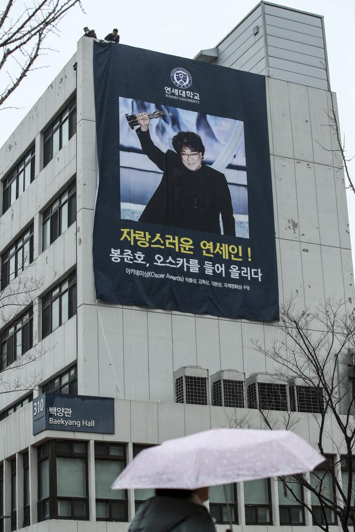 2020年2月12日,南韓首爾,奉俊昊憑藉電影《上流寄生族》獲得四個奧斯卡獎,慶祝的橫幅掛在他的母校延世大學大樓的牆上。