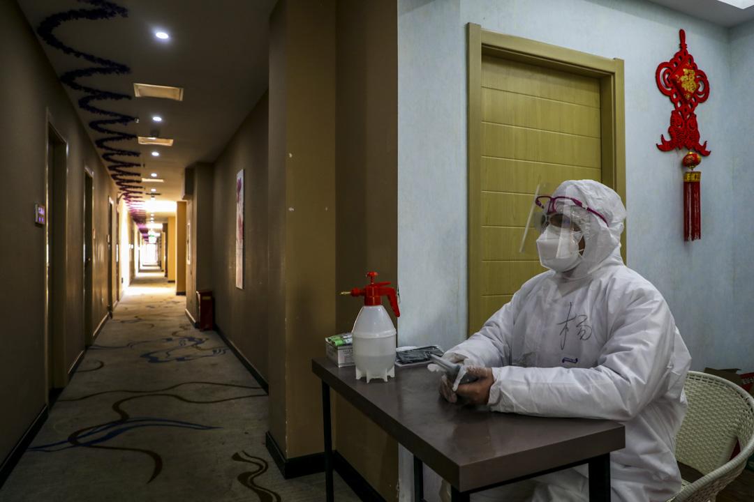 2020年2月3日,湖北省武漢一家旅館,一位穿著保護衣的員工負責接待。