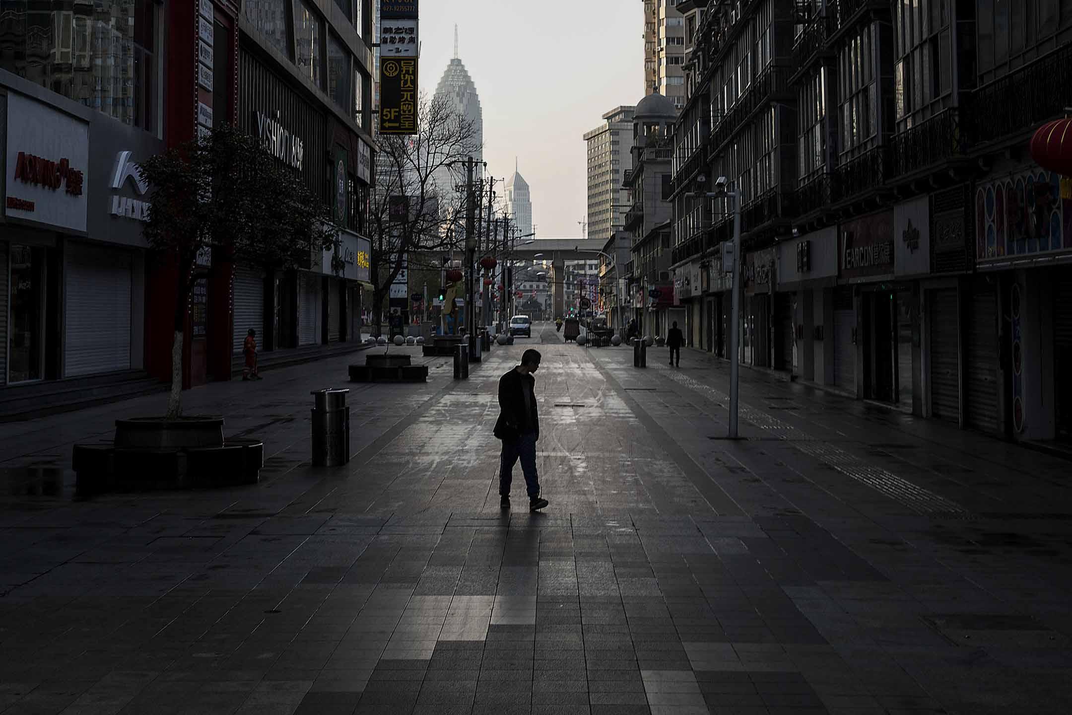 2020年2月13日,武漢一名路人在空蕩蕩的商店街上行走。 攝:Stringer/Getty Images