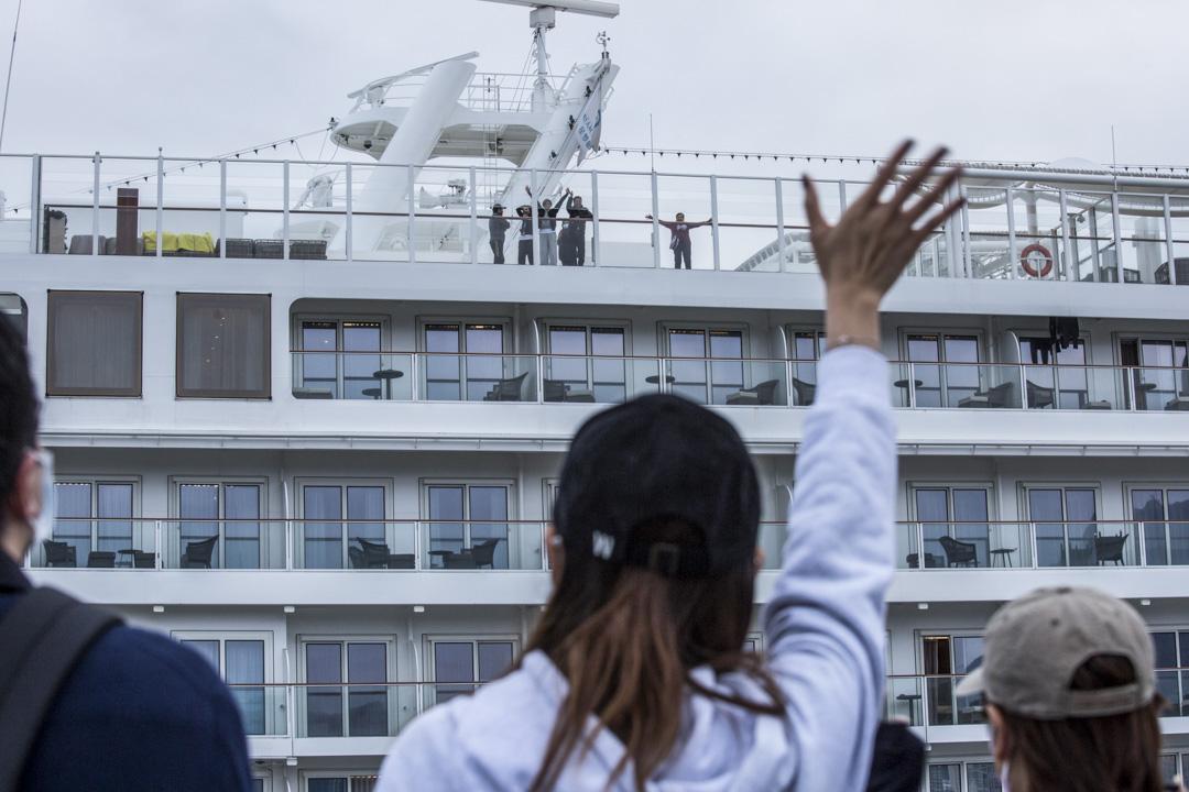 2020年2月8日,曾接載確診感染新型冠狀病毒內地旅客的「世界夢號」郵輪,繼續停泊啟德郵輪碼頭,有市民在對岸向親友遙距揮手問好。 攝:林振東/端傳媒