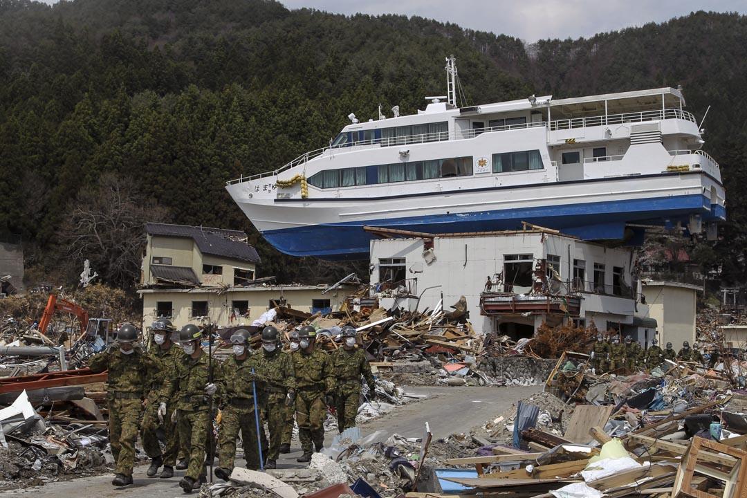 2011年4月25日,日本自衛隊成員在岩手縣搜索地震和海嘯的遇難者遺體。