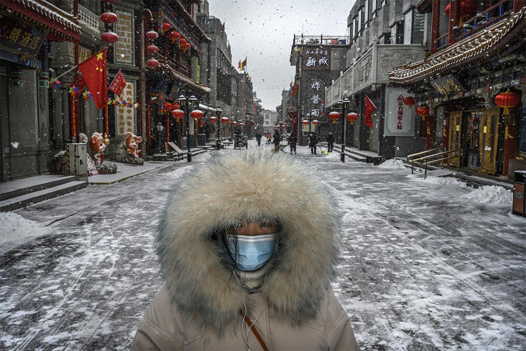 2020年2月5日,一名中國婦女戴著一個口罩走在一條被關閉的商業街。 攝:Kevin Frayer/Getty Images