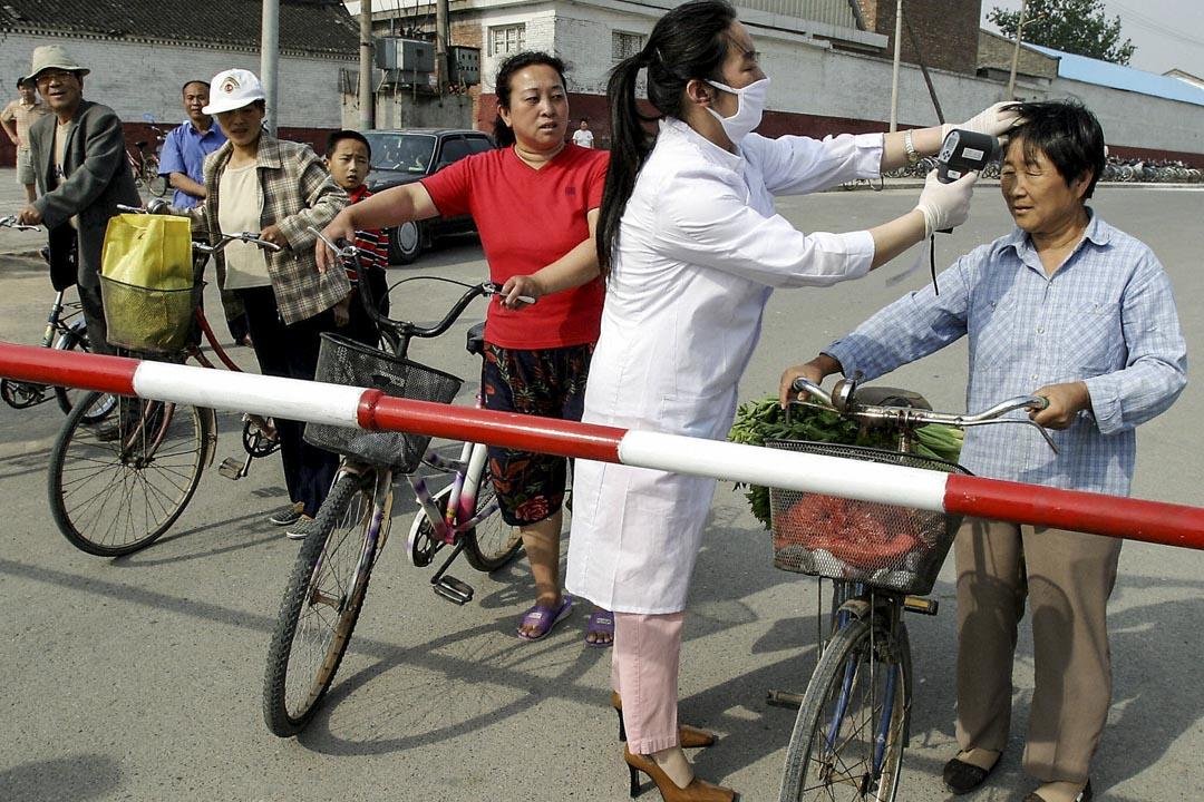 2003年6月8日,政府工作人員在通往北京居民區的路障前替進入的市民檢查體溫。