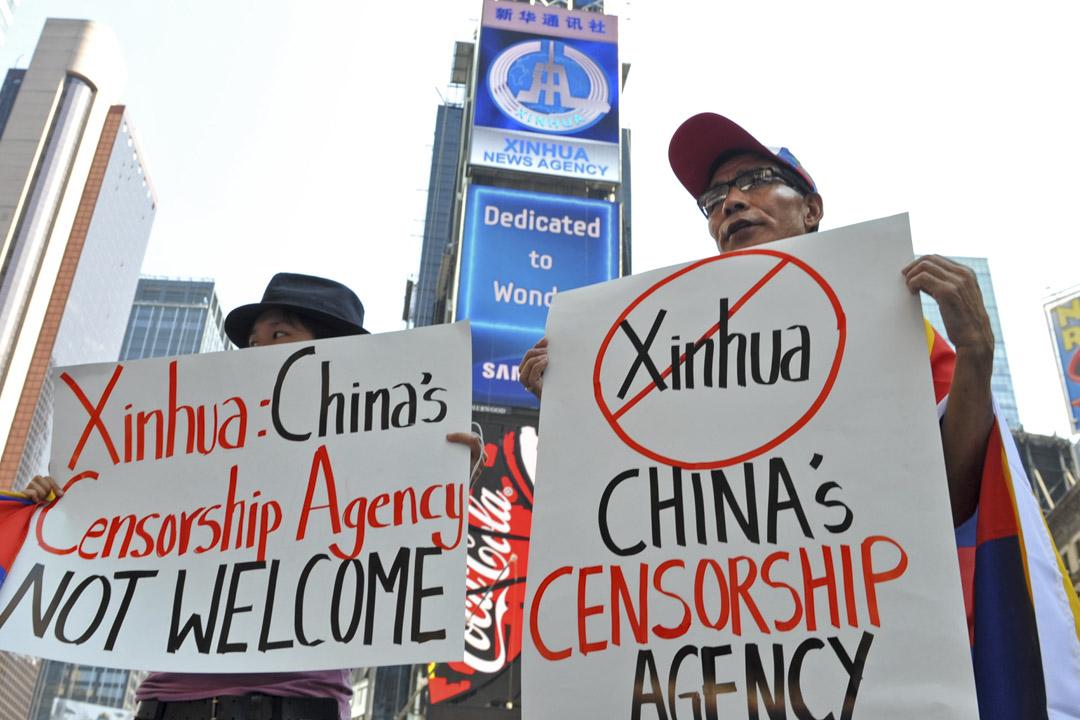 美國認定五家中國官方媒體機構為「外國使團」,等同中國政府的一部分。圖為2011年8月1日,新華社在紐約時代廣場租用新電子廣告牌,當地學生在廣告牌下抗議。 攝:Stan Honda/AFP via Getty Images