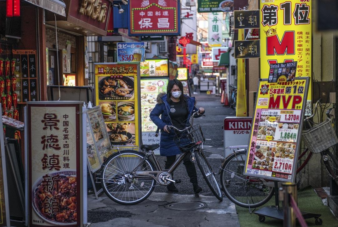 2020年2月13日,日本橫濱一位戴著口罩的女士騎單車。