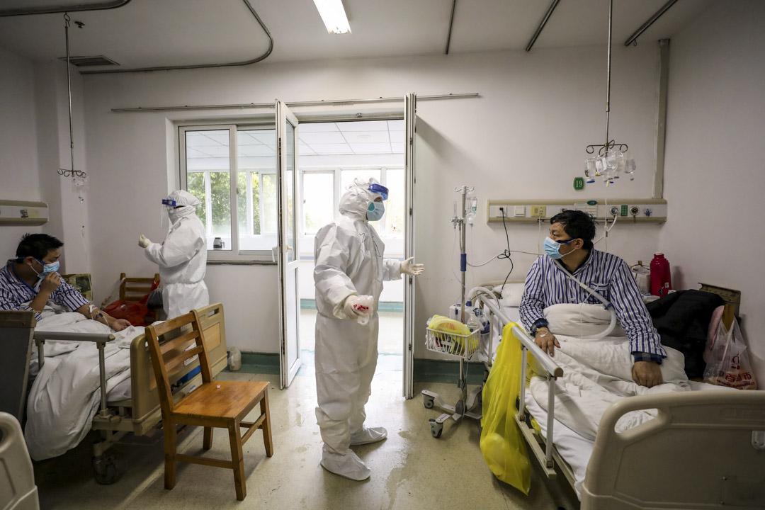 2020年2月13日,醫務人員將在武漢的醫院檢查患者的病情。