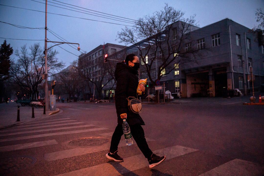 2020年1月28日,北京一名市民戴著口罩外出購買日用品。