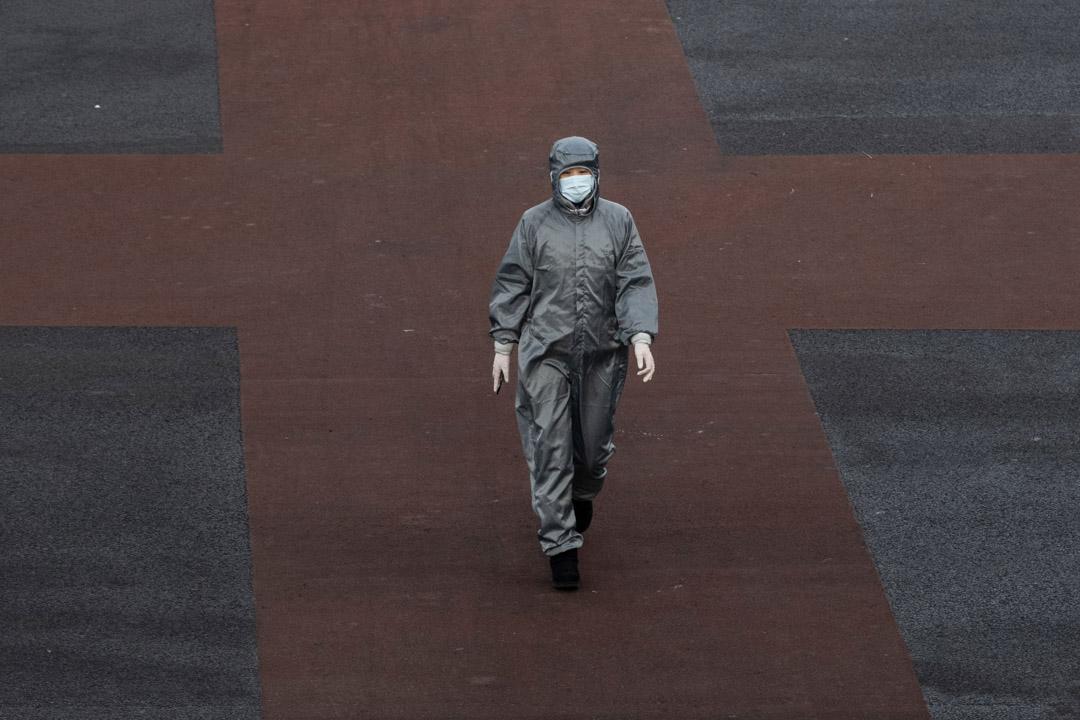 2020年2月8日,北京一名穿著防護服和口罩的中國婦女越過一條空曠的街道十字路口。