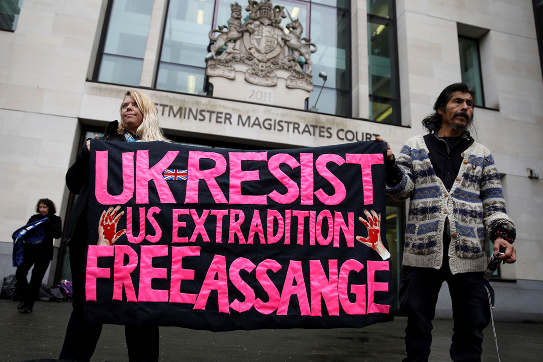 2020年2月19日在英國倫敦西敏裁判法院外,有示威者手持標語,促請英國政府及法院拒絕美方針對「維基解密」創辦人阿桑奇(Julian Assange)提出的引渡申請。 攝:Tolga Akmen / AFP / Getty Images