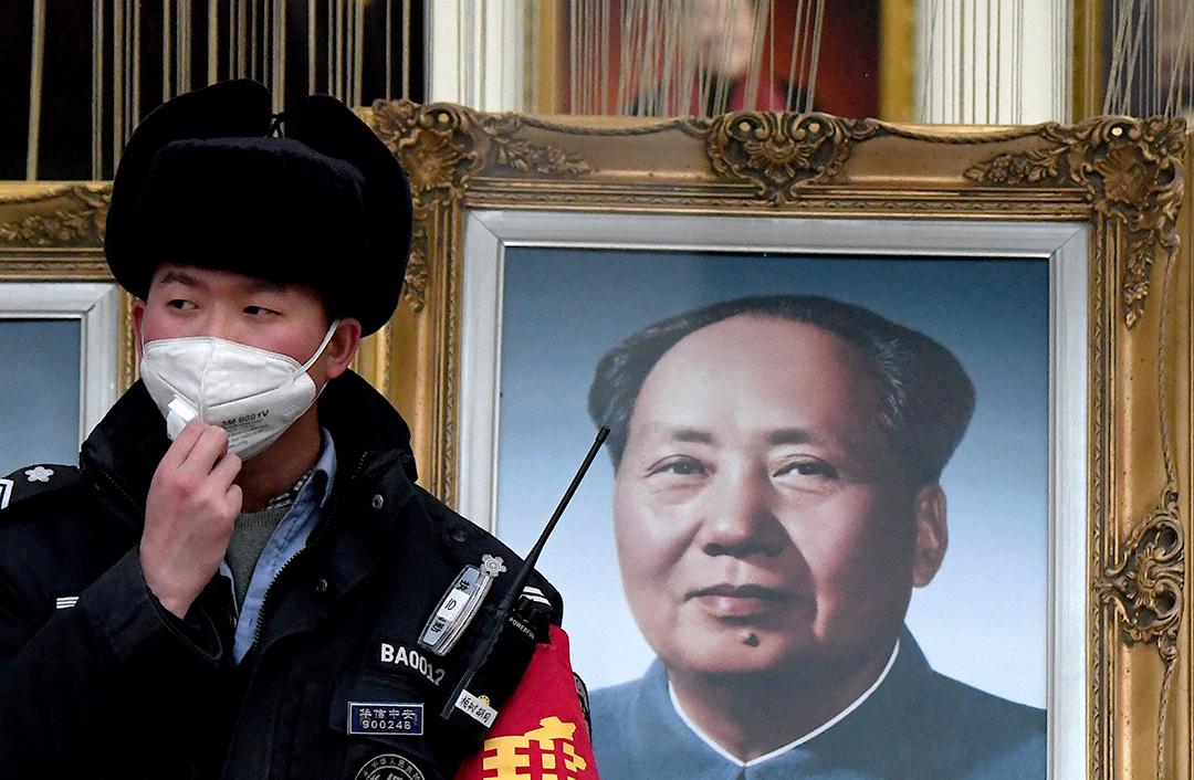 2020年1月27日,北京一名警衛戴著口罩站在毛澤東的畫像旁。 攝: Noel Celis/AFP via Getty Images