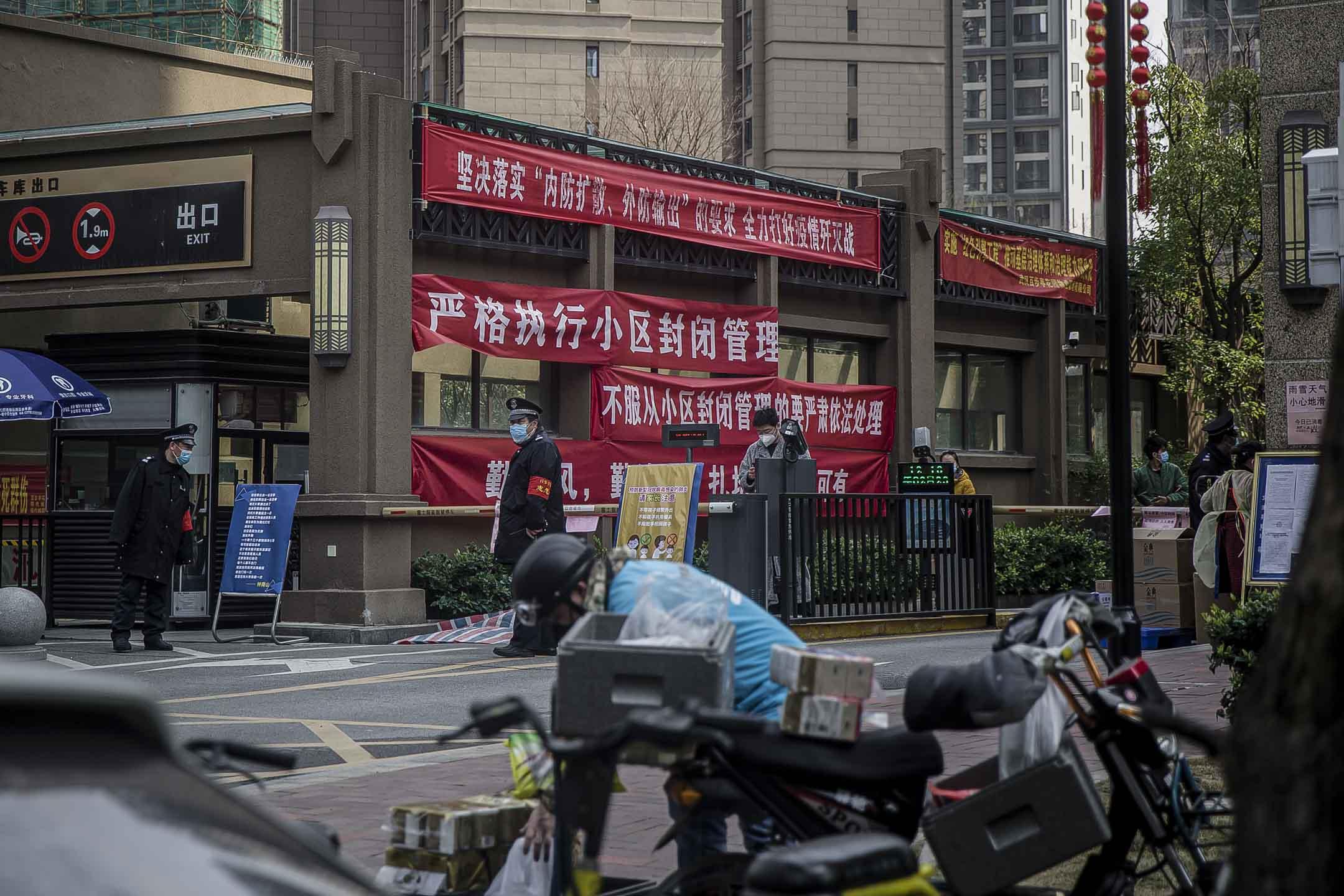 百步亭小區封閉後,武漢居民和快遞員只能在門口交接包裹。 攝:Gerry Yin/端傳媒