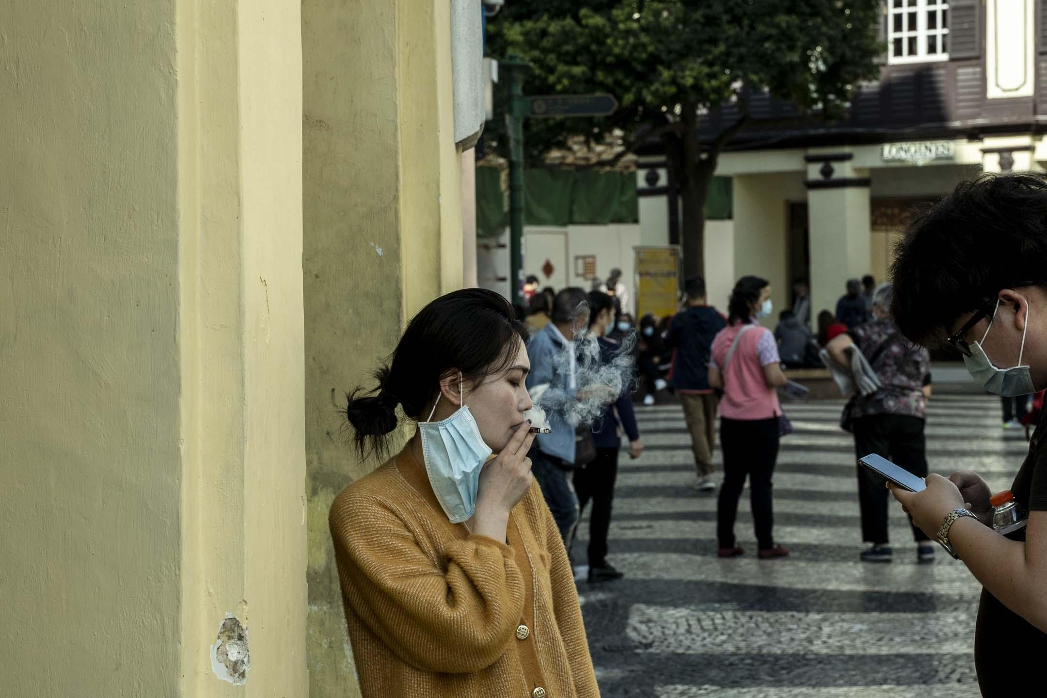 2020年2月23日,澳門的一名旅客,除下口罩抽了一支煙。 攝:林振東/端傳媒