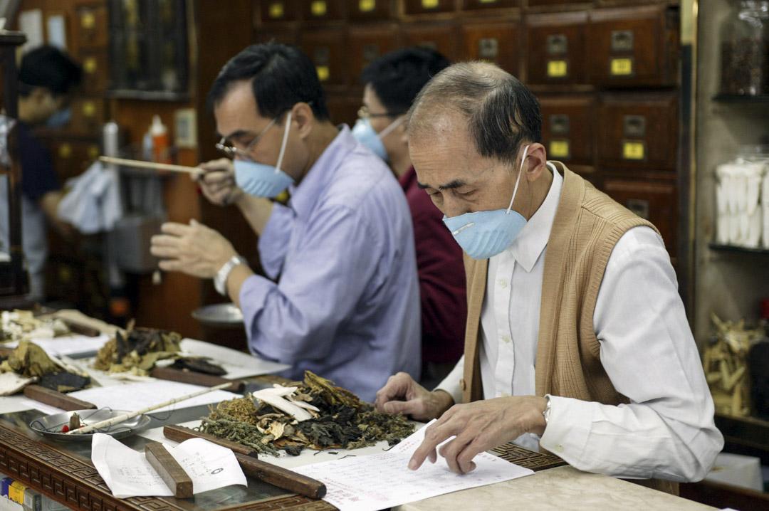 2003年3月28日,SARS肆虐期間的香港一家中藥店,工作中的醫師們。