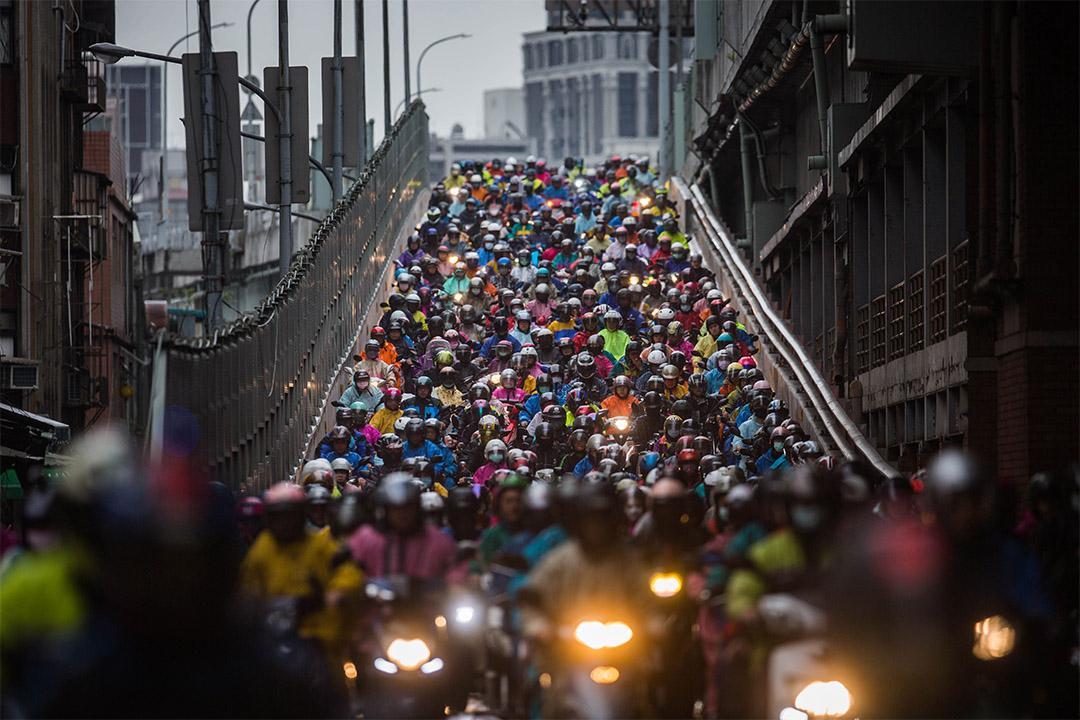 2020年3月12日,台北的市民戴上口罩騎著機車上班。