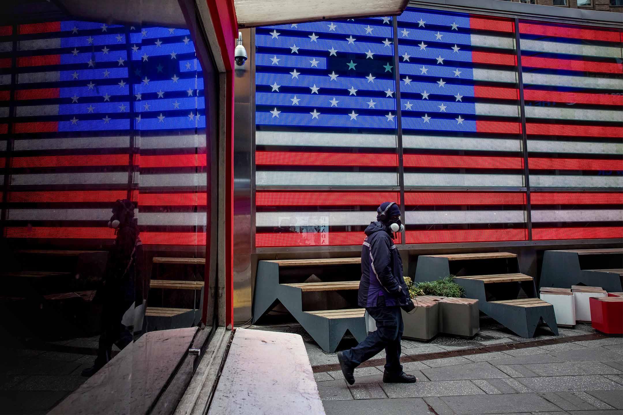 2020年3月19日,一名戴著防毒面罩的FedEx員工於美國紐約時代廣場走過。 攝:Michael Nagle/Bloomberg via Getty Images