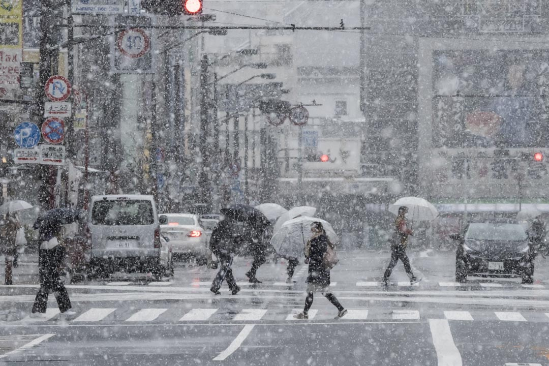 2020年3月29日,日本東京降雪,人們戴著口罩在淺草區過馬路。