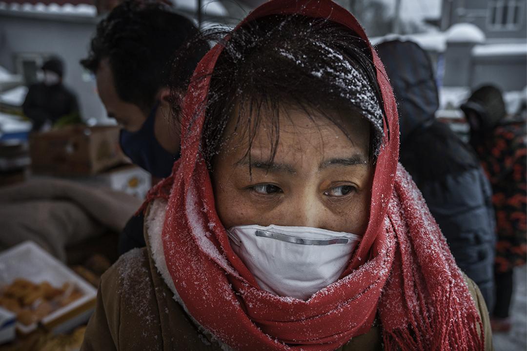 2020年2月6日中國北京,一名中國婦女戴著口罩在一個市場上購物。