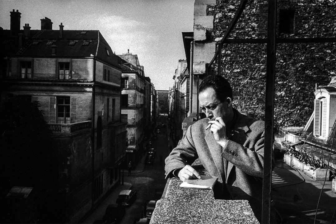 1955年法國作家卡繆斯在他出版社辦公室外面的陽台上抽煙。 攝:Loomis Dean/The LIFE Picture Collection via Getty Images