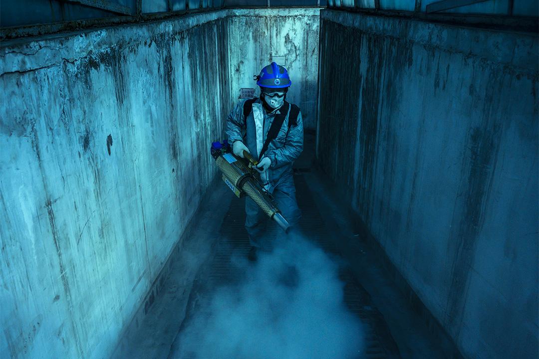 2020年3月5日中國北京,一名志願者穿著防護服為當地住宅區的公共區域進行消毒。 攝:Kevin Frayer/Getty Images