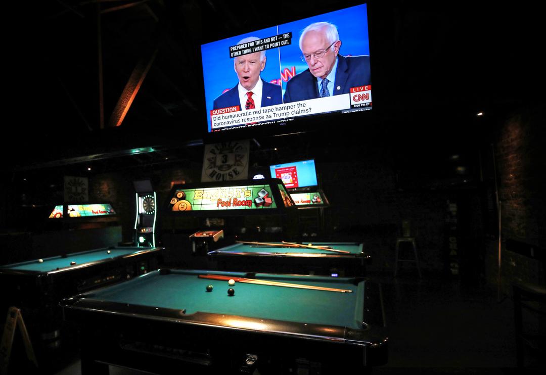 2020年3月15日,洛杉磯一家酒吧裡播放著民主黨初選總統候選人拜登與桑德斯的辯論節目。