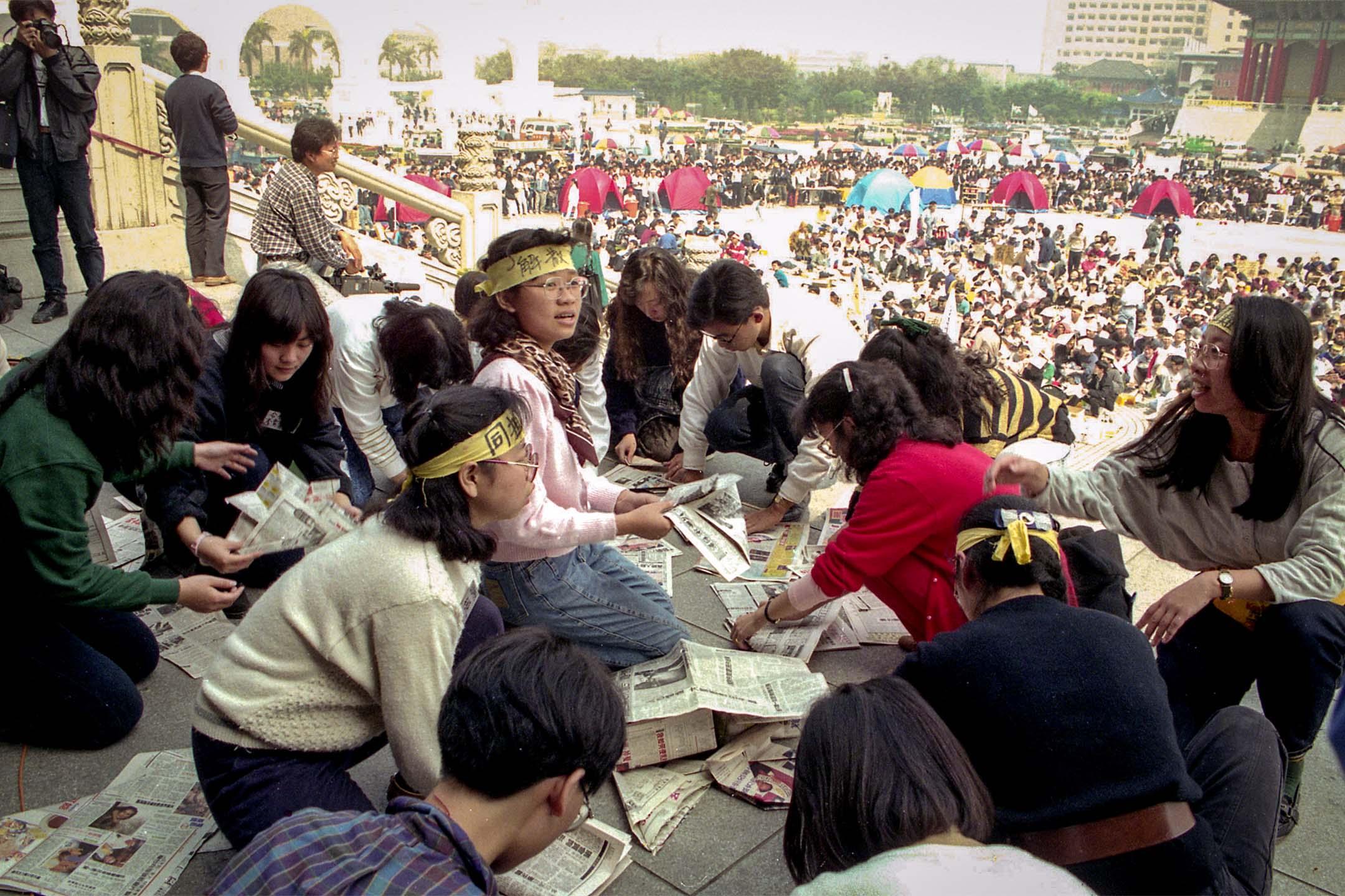 1990年3月20日上午陽光普照,野百合學運學生在中正紀念堂廣場上的情況,他們靜坐並用報紙製作帽子遮太陽。 攝:郭日曉/中央社