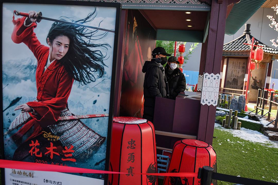 """2020年2月16日,兩名職員戴著口罩在北京一家幾乎空蕩的購物中心內為迪士尼""""花木蘭""""的攤位做準備。  攝:Greg Baker/AFP via Getty Images"""