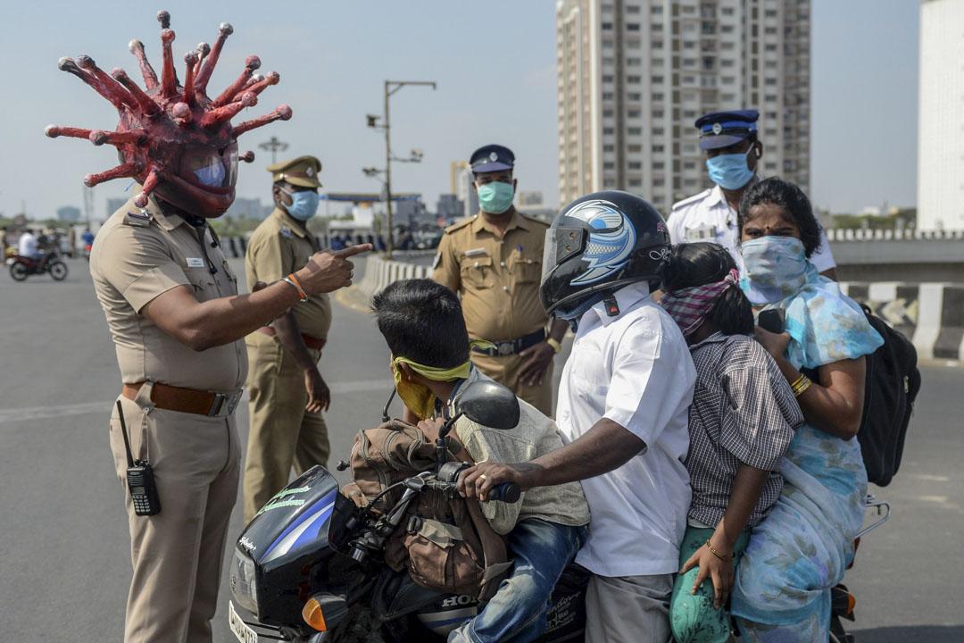 2020年3月28日,印度政府實施的全國封鎖期間,清奈檢查站一位警察戴著以冠狀病毒為主題的頭盔,與騎著電單車的一家人交談。