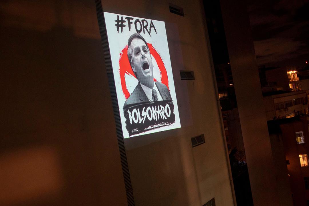2020年3月26日在巴西里約熱內盧,有民眾將總統博爾索納盧的肖像及 #ForaBolsonaro 標語投影至大廈外牆,以抗疫總統無視疫情對民眾的威脅。 攝:Mauro Pimentel / AFP via Getty Images