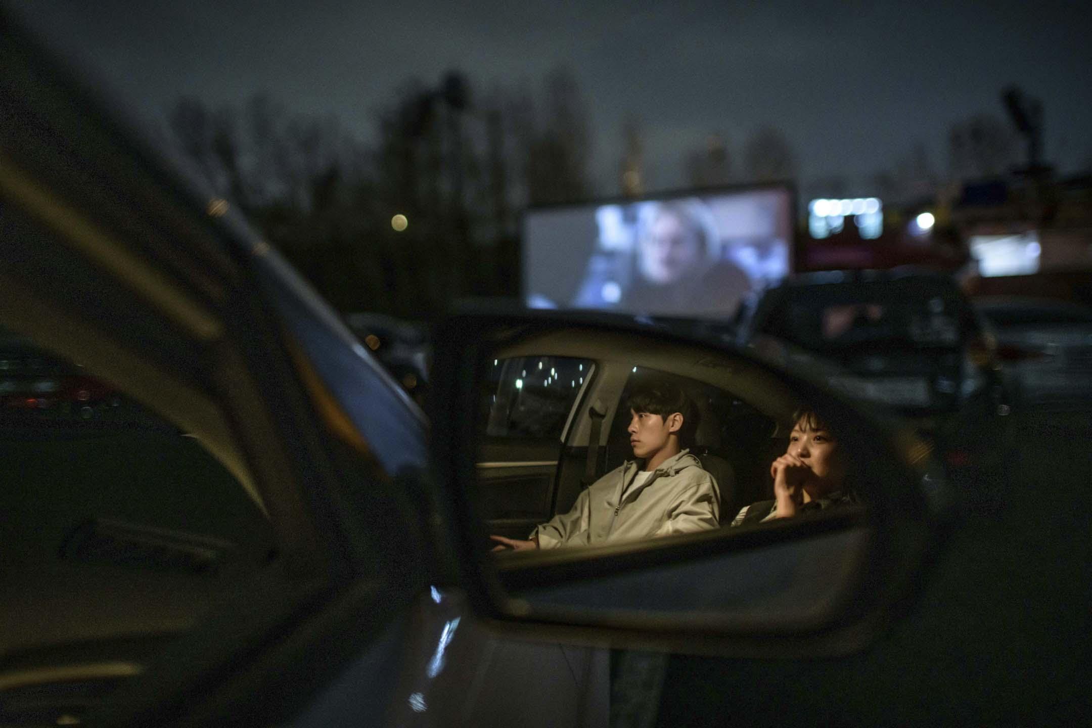 2020年3月21日,南韓首爾汽車影院,一對夫婦坐在車裡觀看電影放映。 攝:Ed Jones/AFP via Getty Images