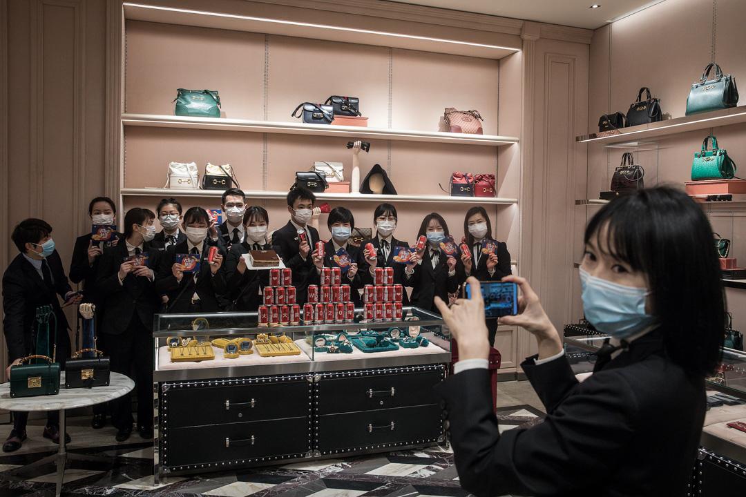 2020年3月30日,武漢的部份商場重開,服飾店員工在復工前拍照留念。