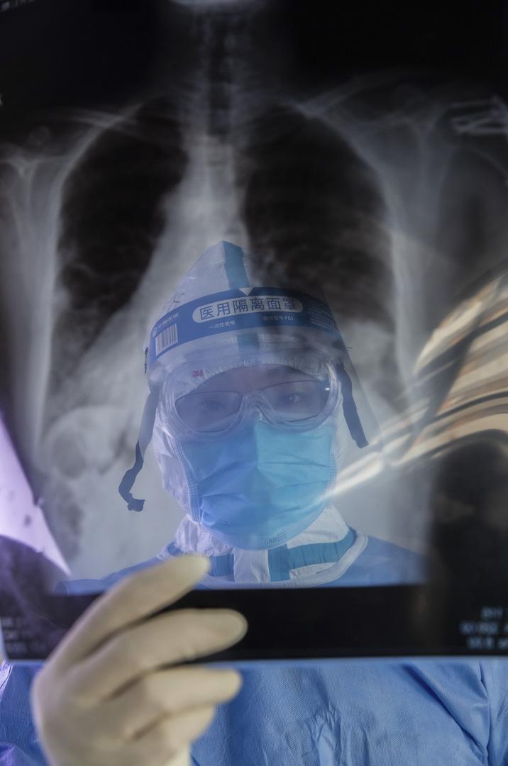 2020年2月22日,武漢一間醫院的醫生為新冠病毒隔離病房的病人進行診療。
