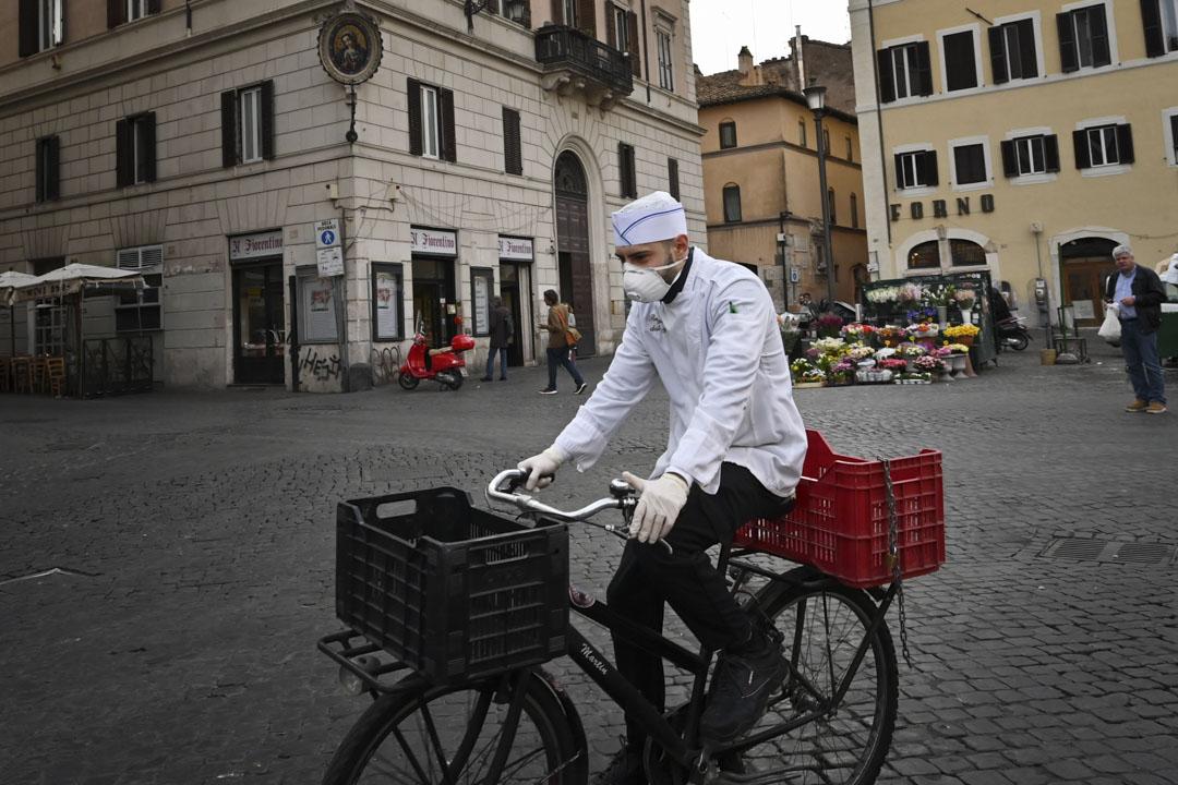 2020年3月10日,一名戴著口罩的廚師騎單車穿越羅馬一個空無一人的廣場。