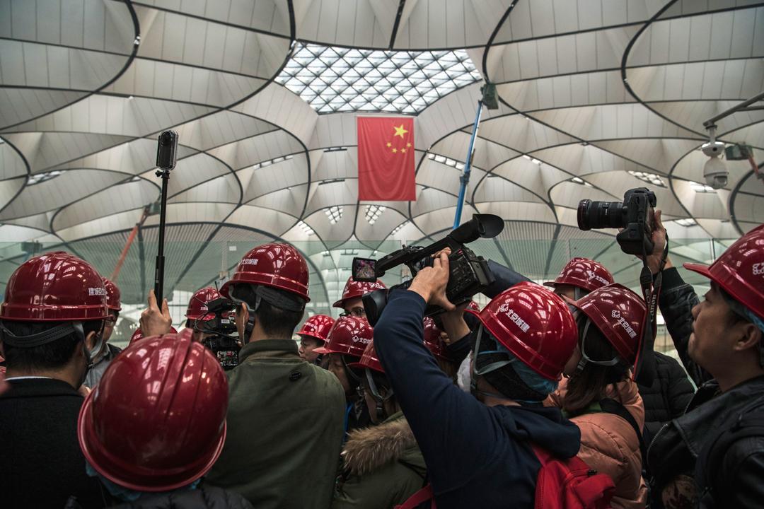 2019年3月1日,一群記者正在訪問興建中的北京大興國際機場的一名工程師。