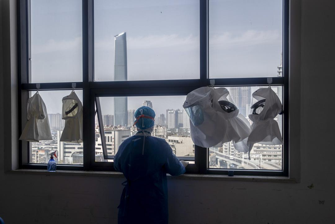 2020年3月19日,武漢的一家醫院在治療COVID-19冠狀病毒患者後,一名醫務人員從更衣室的窗戶向外張望。