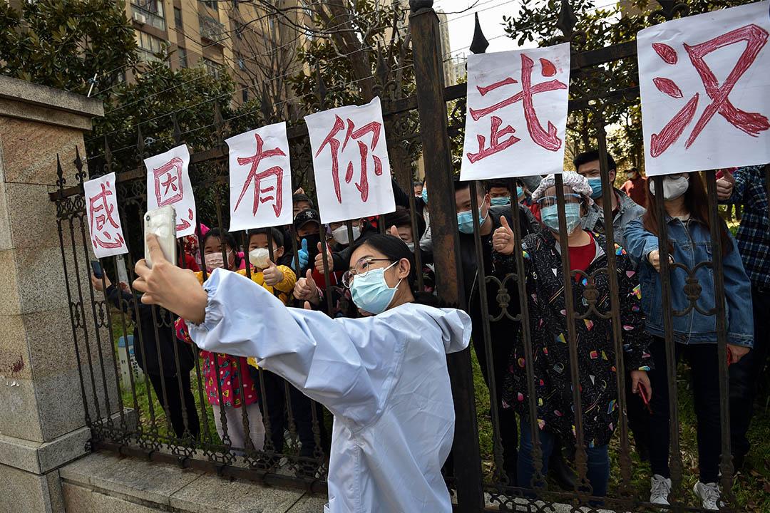 2020年3月18日中國中部湖北省武漢市,一名來自雲南醫療隊的人員與當地人自拍。