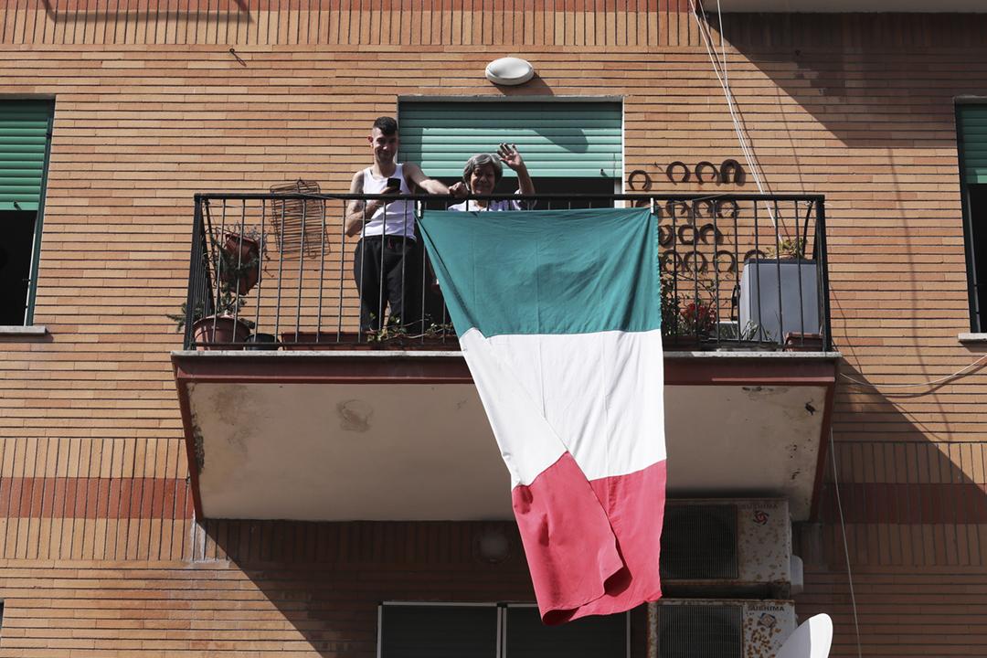 2020年3月15日在意大利羅馬,因應疫情而待在家中的民眾,走到露台向街上的攝影師揮手。 攝:Marco Di Lauro / Getty Images
