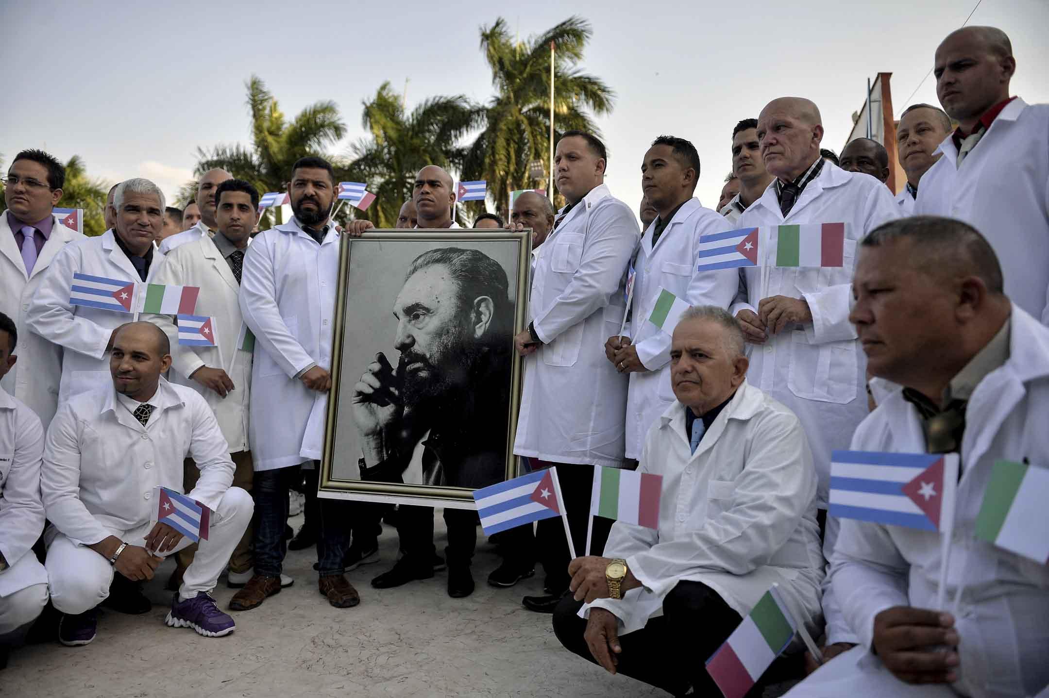 2020年3月21日,古巴亨利·雷芙國際醫療隊的醫護人員準備前往意大利抗疫,出發前與古巴前領袖卡斯特羅的肖像合照。 攝:Yamil Lage / AFP via Getty Images
