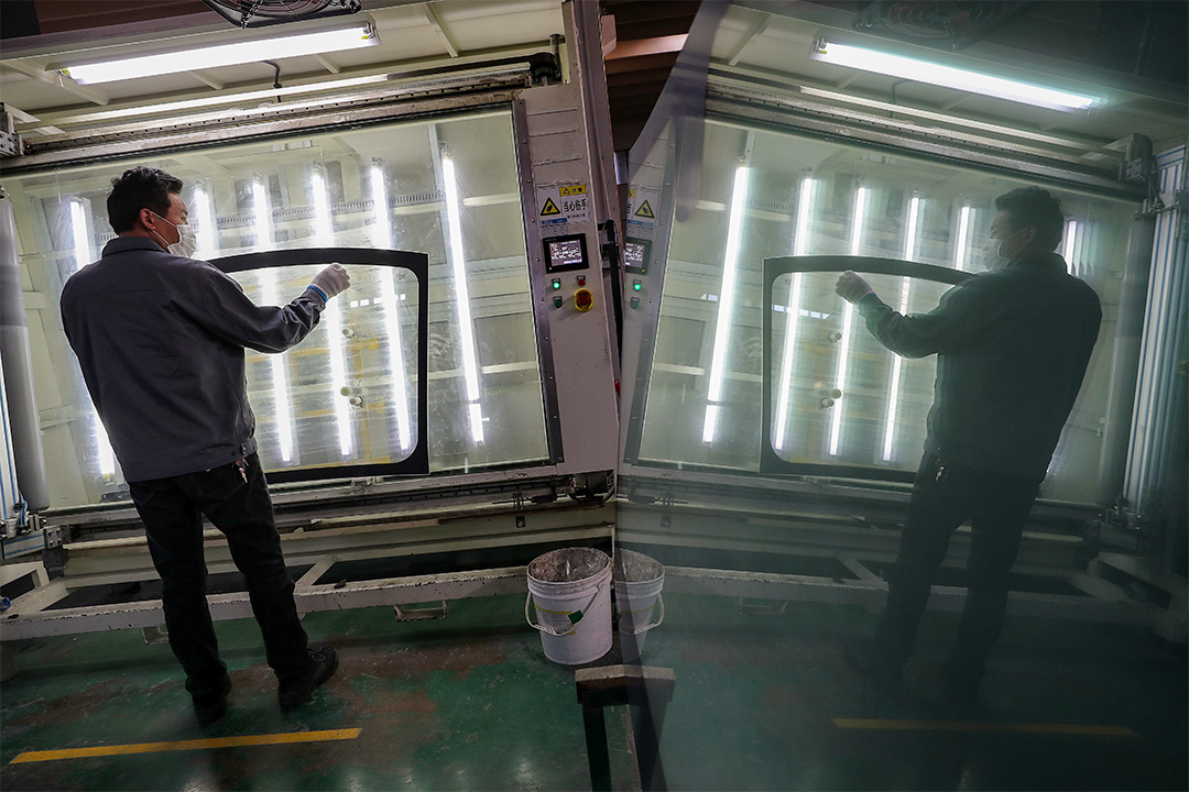 2020年3月4日南通,一名戴口罩的工人在汽車擋風玻璃廠內工作。