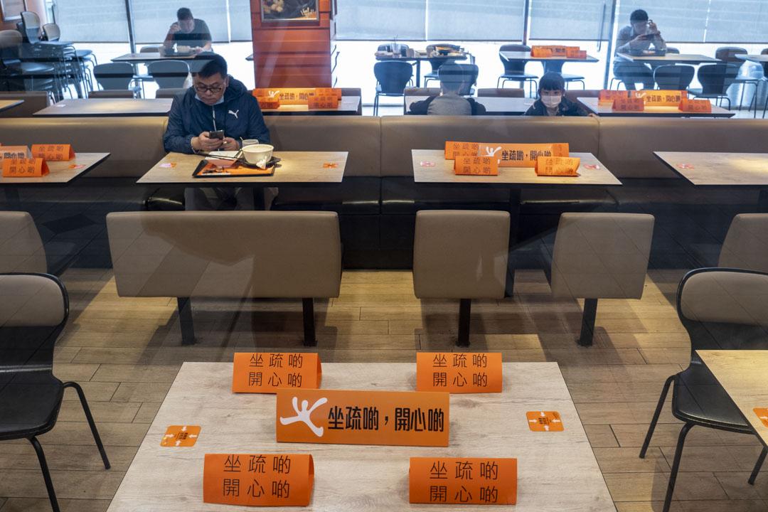 2020年3月29日,政府實施「限客令」,食肆每張桌相隔最少1.5米、座位減半、每枱上限4人。有連鎖快餐店以標語提醒顧客。 攝:林振東/端傳媒
