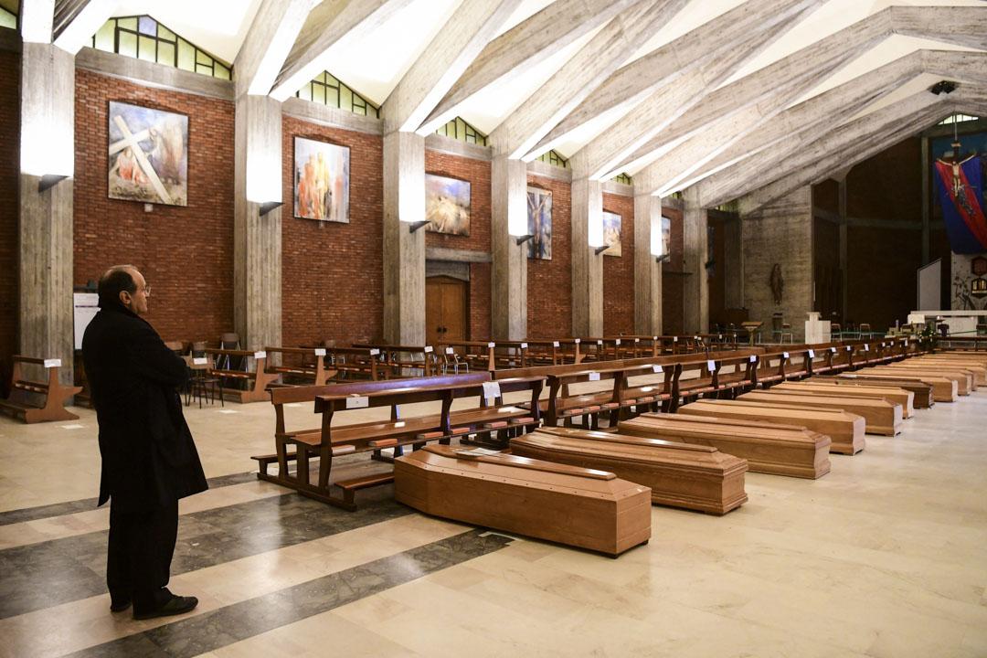2020年3月26日,意大利一間教堂,牧師站在棺木前。