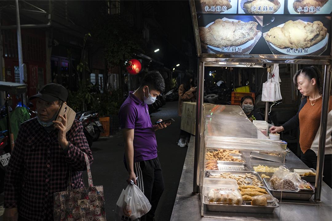 2020年3月12日龍山寺附近的夜市,一名客人等候他的雞排。