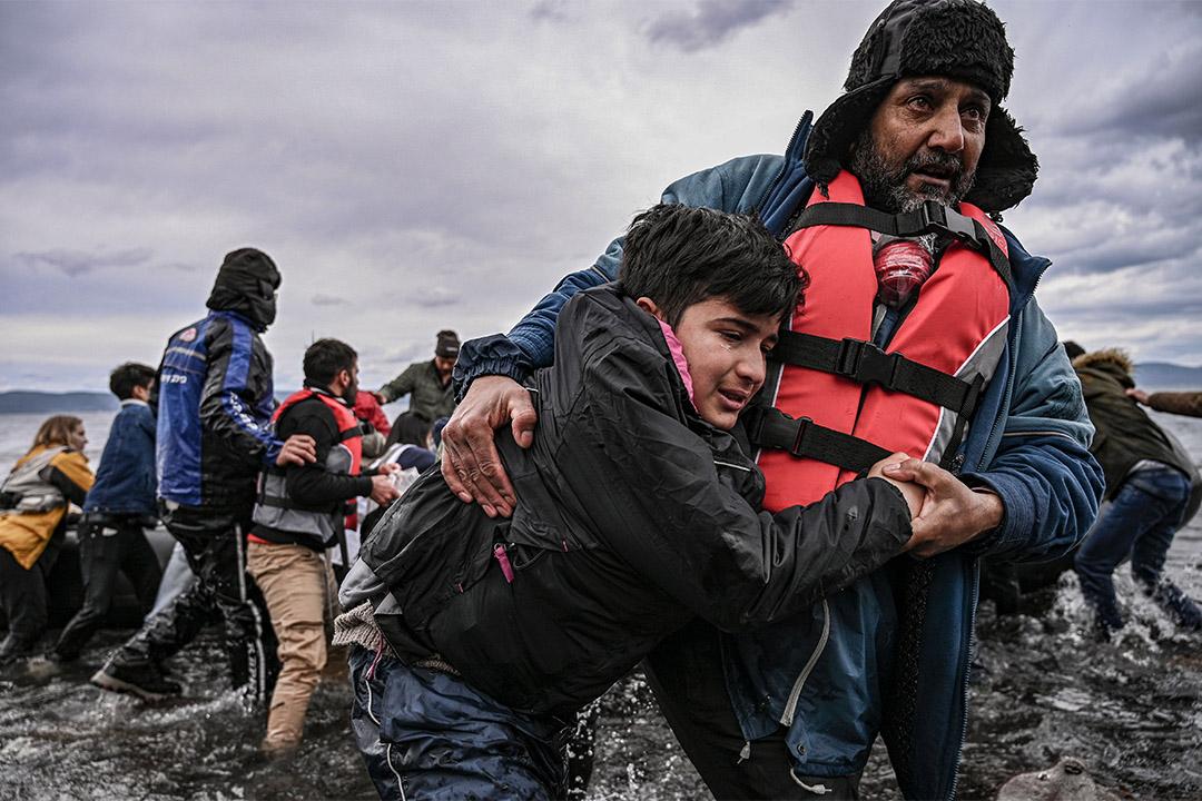 2020年2月28日,一名男子幫助一個男孩登陸希臘萊斯博斯島,54名阿富汗難民乘小艇上岸意圖前往歐洲。