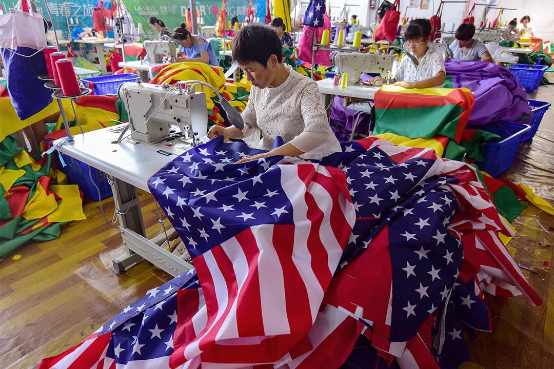 2018年7月13日,中國安徽省阜陽市的中國員工在一家工廠縫製美國國旗。