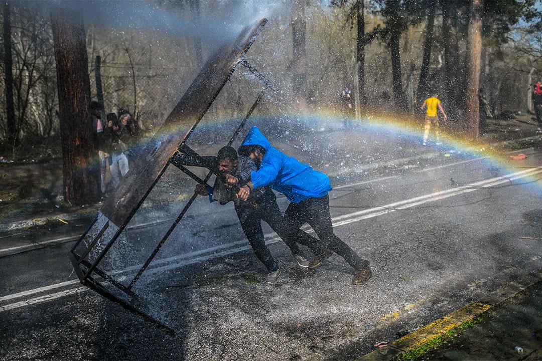 2020年3月7日,難民在土耳其希臘邊境以桌子抵擋希臘警方的水砲。 攝:Bulent Kilic/AFP via Getty Images