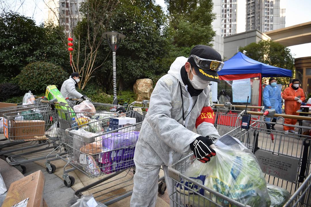 2020年2月18日在中國湖北省武漢市,社區工作人員正分配物資,準備送進小區分發予被禁止外出的住戶。 圖片來源:Feature China / Barcroft Media via Getty Images