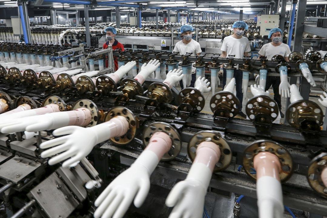 2020年3月23日,中國安徽淮北的一家工廠,工人在生產醫用手套。 攝:STR/AFP via Getty Images