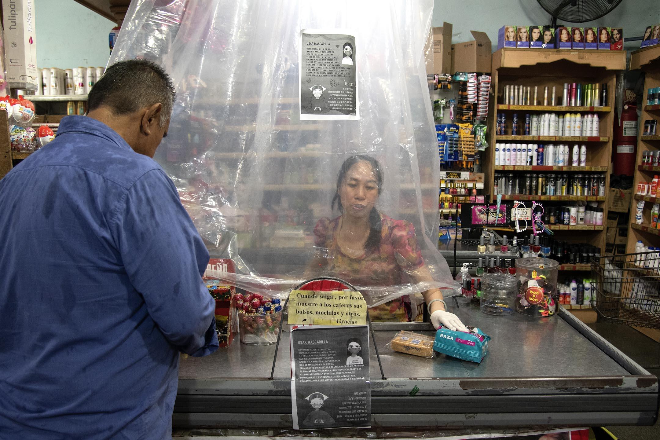 2020年3月14日,阿根庭的一家超市內,售貨員隔著膠簾工作。 攝: Lalo Yasky/Getty Images