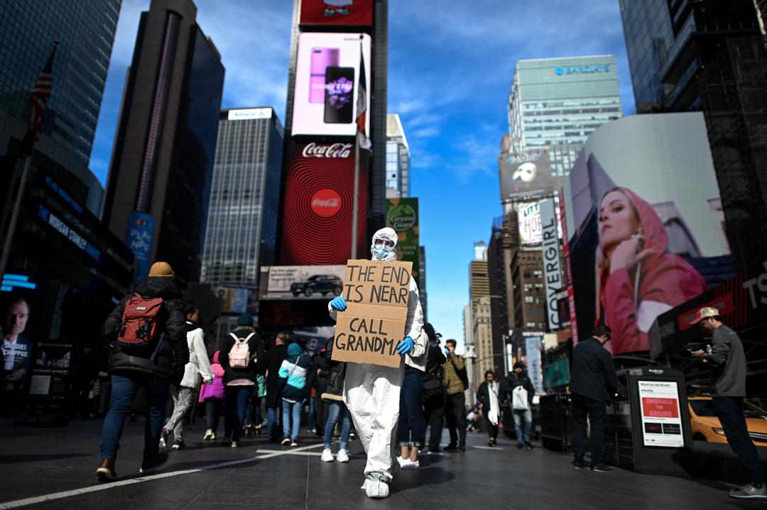 2020年3月13日,紐約時代廣場有人穿上保護衣,舉起「末日將至,打給外婆」的手舉牌。