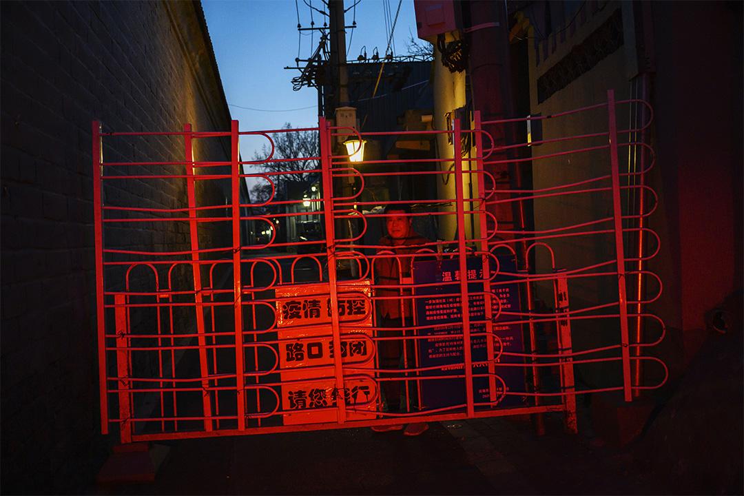 2020年3月15日北京,在防止外人進入胡同的路障內有一個不戴口罩的居民。