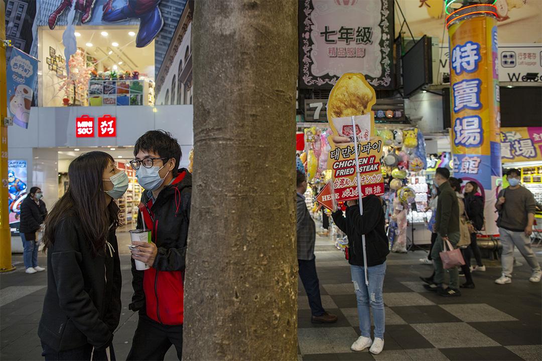 2020年3月11日西門町,有人拿著廣告板叫賣雞排。